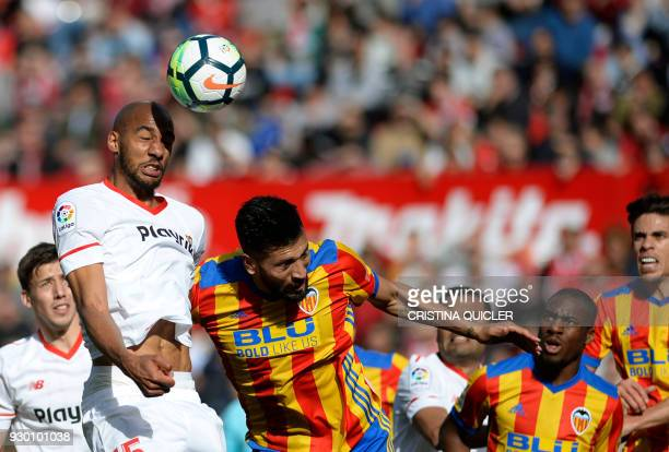 Sevilla's French midfielder Steven N'Zonzi heads the ball with Valencia's Argentinian defender Ezequiel Garay during the Spanish league football...