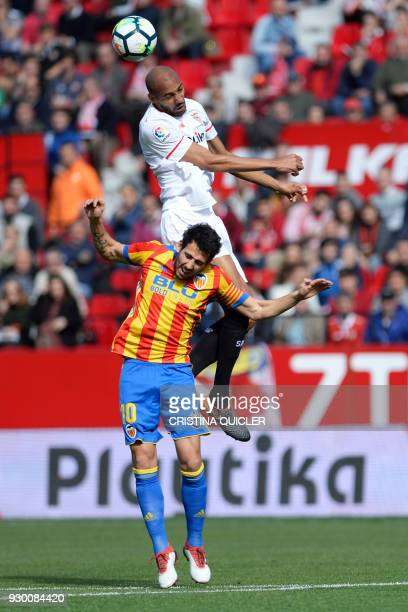 Sevilla's French midfielder Steven N'Zonzi jumps to head the ball with Valencia's Spanish midfielder Daniel Parejo during the Spanish league football...