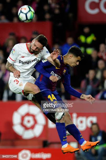 Sevilla's Mexican defender Miguel Layun jumps for the ball with Barcelona's Brazilian midfielder Philippe Coutinho during the Spanish League football...