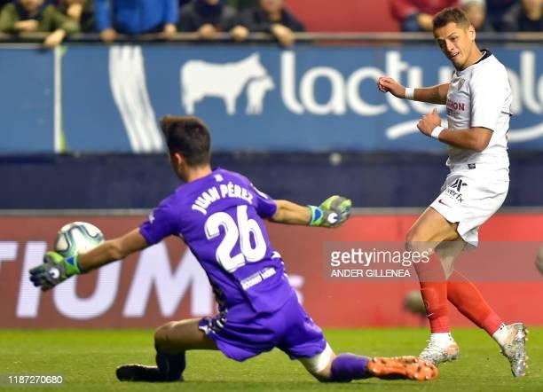 Sevilla's Mexican forward Chicharito shoots the ball in front of Osasuna's Spanish goalkeeper Juan Perez during the Spanish league football match...