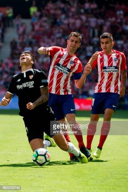 Sevilla's midfielder from Argentina Joaquin Correa vies with Atletico Madrid's midfielder from Spain Gabi beside Atletico Madrid's forward from...