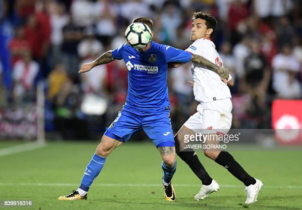 Sevilla's midfielder Jesus Navas vies with Getafe's Portuguese defender Gabriel Antunes during the Spanish league football match Getafe CF vs Sevilla...