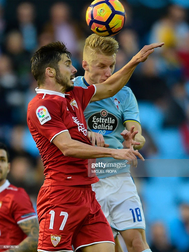 Sevilla's midfielder Pablo Sarabia (L) jumps for the ball with Celta Vigo's Danish midfielder Daniel Wass during the Spanish league football match RC Celta de Vigo vs Sevilla FC at the Balaidos stadium in Vigo on December 11, 2016. / AFP / MIGUEL
