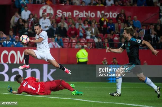 Sevilla's midfielder Pablo Sarabia scores past Real Sociedad's Argentinian goalkeeper Geronimo Rulli and midfielder Asier Illarramendi during the...