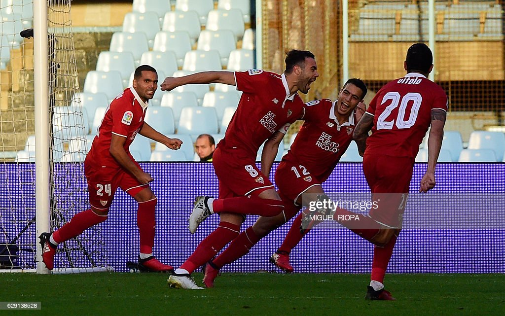 Sevilla's midfielder Vicente Iborra (2ndR) celebrates with teammates after scoring during the Spanish league football match RC Celta de Vigo vs Sevilla FC at the Balaidos stadium in Vigo on December 11, 2016. / AFP / MIGUEL