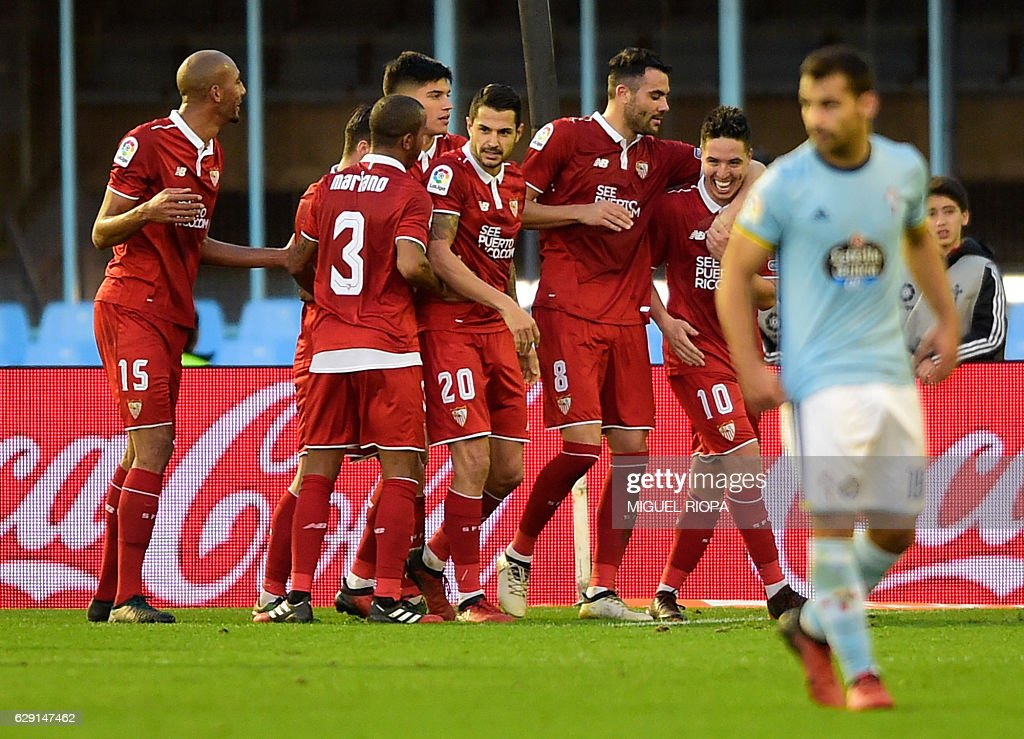 Sevilla's midfielder Vicente Iborra (2ndR) is congratulated by teammates after scoring during the Spanish league football match RC Celta de Vigo vs Sevilla FC at the Balaidos stadium in Vigo on December 11, 2016. Sevilla won 3-0. / AFP / MIGUEL