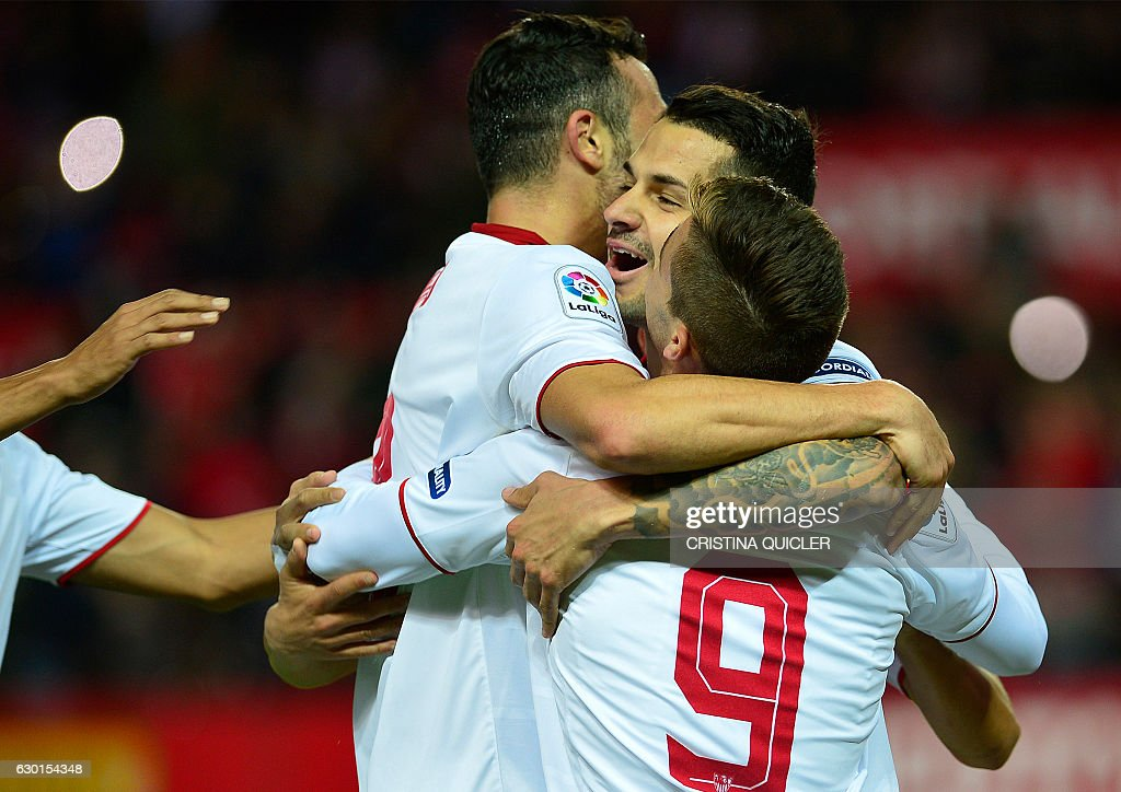 Sevilla's midfielder Vitolo (2R) celebrates after scoring a goal during the Spanish league football match Sevilla FC vs Malaga CF at the Ramon Sanchez Pizjuan stadium in Sevilla on December 17, 2016. / AFP / CRISTINA