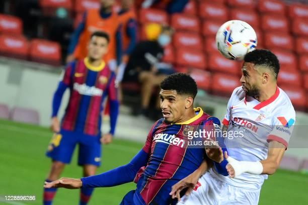 Sevilla's Moroccan forward Youssef EnNesyri heads the ball next to Barcelona's Uruguayan defender Ronald Federico Araujo da Silvaduring the Spanish...