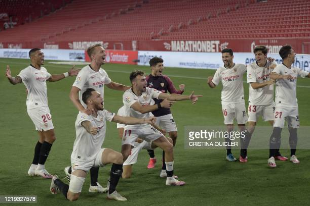 Sevilla's players celebrate at the end of the Spanish League football match between Sevilla FC and Real Betis at the Ramon Sanchez Pizjuan stadium in...