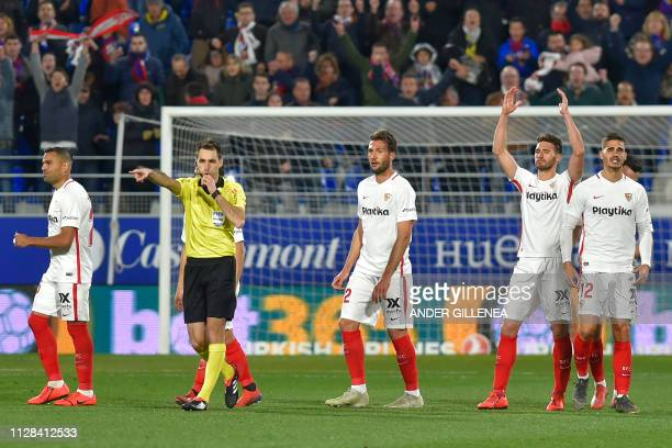 Sevilla's players react after Huesca's scored a second goal during the Spanish league football match between SD Huesca and Sevilla FC at the El...