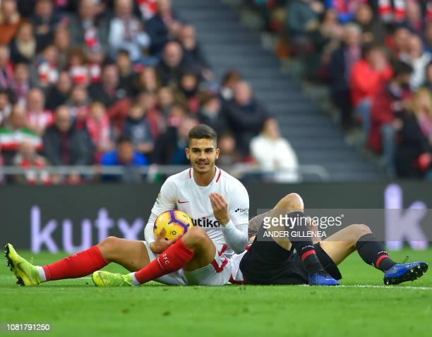 Sevilla's Portuguese forward Andre Silva and Athletic Bilbao's Spanish defender Inigo Martinez lie on the ground during the Spanish League football...