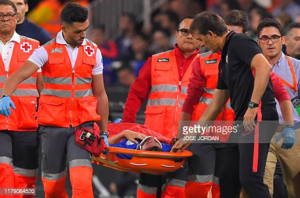 Sevilla's Spanish coach Julen Lopetegui looks at his Sevilla's Spanish defender Sergio Escudero being carried away the field on a stretcher after an...
