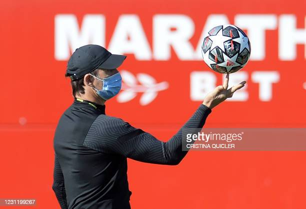 Sevilla's Spanish coach Julen Lopetegui plays with a ball during a training session at the Ciudad Deportiva Jose Ramon Cisneros Palacios training...