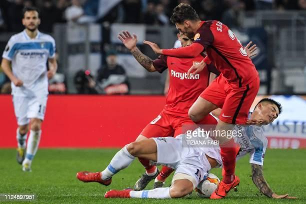Sevilla's Spanish defender Sergi Gomez and Sevilla's Argentine midfielder Ever Banega tackle Lazio's Argentine forward Joaquin Correa during the UEFA...