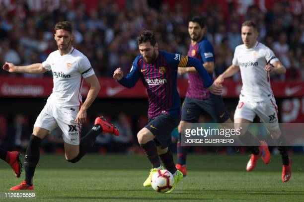 Sevilla's Spanish defender Sergi Gomez fights for the ball with Barcelona's Argentinian forward Lionel Messi during the Spanish league football match...