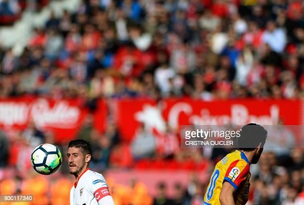 TOPSHOT Sevilla's Spanish defender Sergio Escudero jumps for the ball beside Valencia's Spanish midfielder Daniel Parejo during the Spanish league...