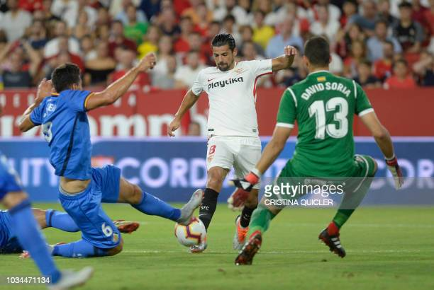 Sevilla's Spanish forward Nolito vies for the ball with Getafe's Spanish goalkeeper David during the Spanish league football match Sevilla FC against...