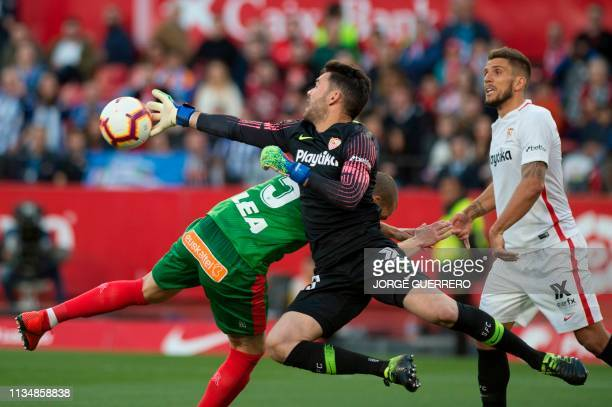Sevilla's Spanish goalkeeper Juan Soriano clears the ball beside Alaves' Spanish defender Victor Laguardia during the Spanish league football match...