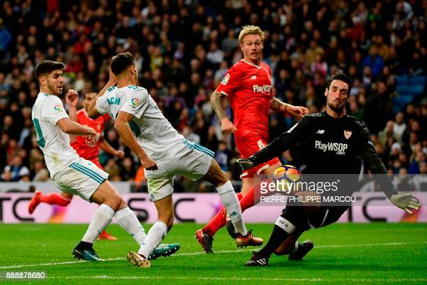 Sevilla's Spanish goalkeeper Sergio Rico Gonzalez blocks a shot on goal by Real Madrid's Moroccan defender Achraf Hakimi next to Real Madrid's...