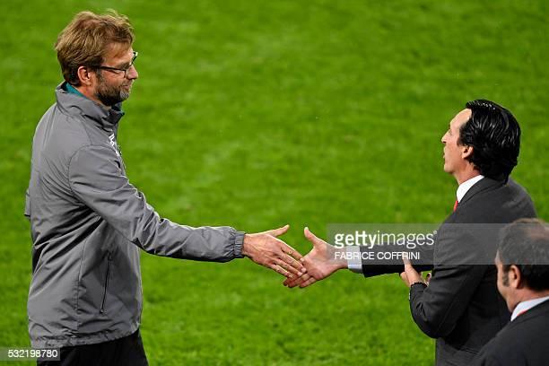 Sevilla's Spanish head coach Unai Emery shakes hands with Liverpool's German head coach Jurgen Klopp after Sevilla won the UEFA Europa League final...