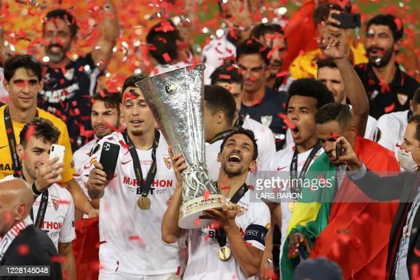 Sevilla's Spanish midfielder Jesus Navas holds the trophy as Sevilla's players celebrate after winning the UEFA Europa League final football match...
