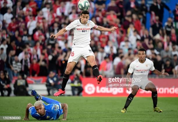 Sevilla's Spanish midfielder Jesus Navas jumps over Getafe´s Brazilian forward Deyverson during the Spanish league football match Getafe CF against...