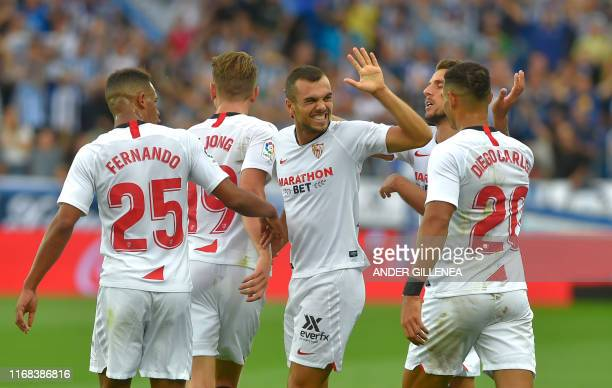 Sevilla's Spanish midfielder Joan Jordan celebrates with teammates after scoring a goal during the Spanish league football match Deportivo Alaves...