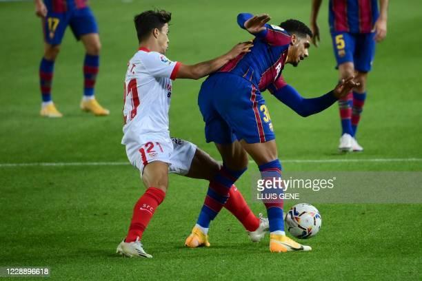 Sevilla's Spanish midfielder Olivier Torres challenges Barcelona's Uruguayan defender Ronald Federico Araujo da Silva during the Spanish League...