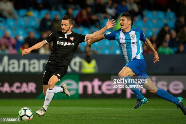Sevilla's Spanish midfielder Pablo Sarabia vies with Malaga's Spanish defender Diego Gonzalez during the Spanish league football match Malaga CF...
