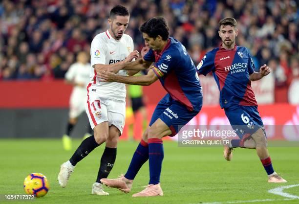 Sevilla's Spanish midfielder Pablo Sarabia vies with SD Huesca's Spanish defender Xabier Etxeita beside SD Huesca's Spanish midfielder Moi Gomez...