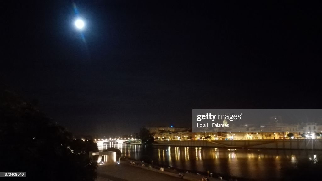 Seville cityscape at night with full moon : Foto de stock