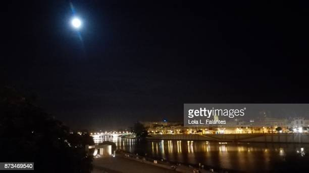 Seville cityscape at night with full moon