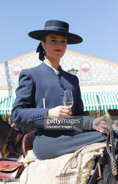 Seville Seville Province Andalusia southern Spain Feria de Abril the April Fair Female rider pauses for refreshment during the horse and carriage...
