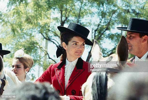 Closeups of Mrs John F Kennedy wearing a typical Andalusian riding outfit rides her horse through the Seville Fair