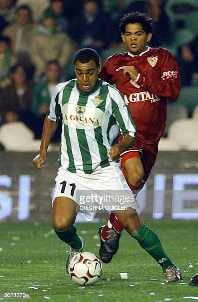 Seville's Brazilian player Daniel Alves follows Betis's Brazilian player Denilson during a Spanish football league match at Ruiz de Lopera's stadium...