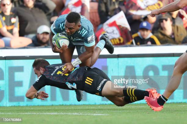 Sevu Reece of the Crusaders dives over the top of Damian McKenzie of the Chiefs during the round 2 Super Rugby match between the Chiefs and the...