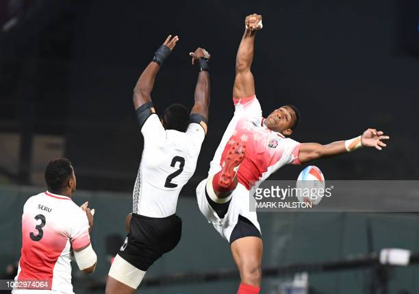 Sevuloni Mocenacagi of Fiji clashes with Jose Coyickai Seru and Jone Naikabula of Japan during their men's round of 16 games at the Rugby Sevens...