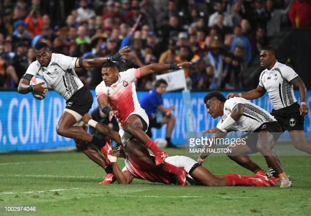 Sevuloni Mocenacagi of Fiji evades the tackle of Japanese players during their men's round of 16 games at the Rugby Sevens World Cup in the ATT Park...