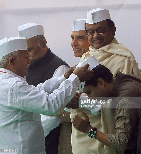 Sewa Dal worker offers a Gandhi cap to Jyotiraditya Scindia Minister of State for Commerce and Industry as Home minister P Chidambaram looks on...