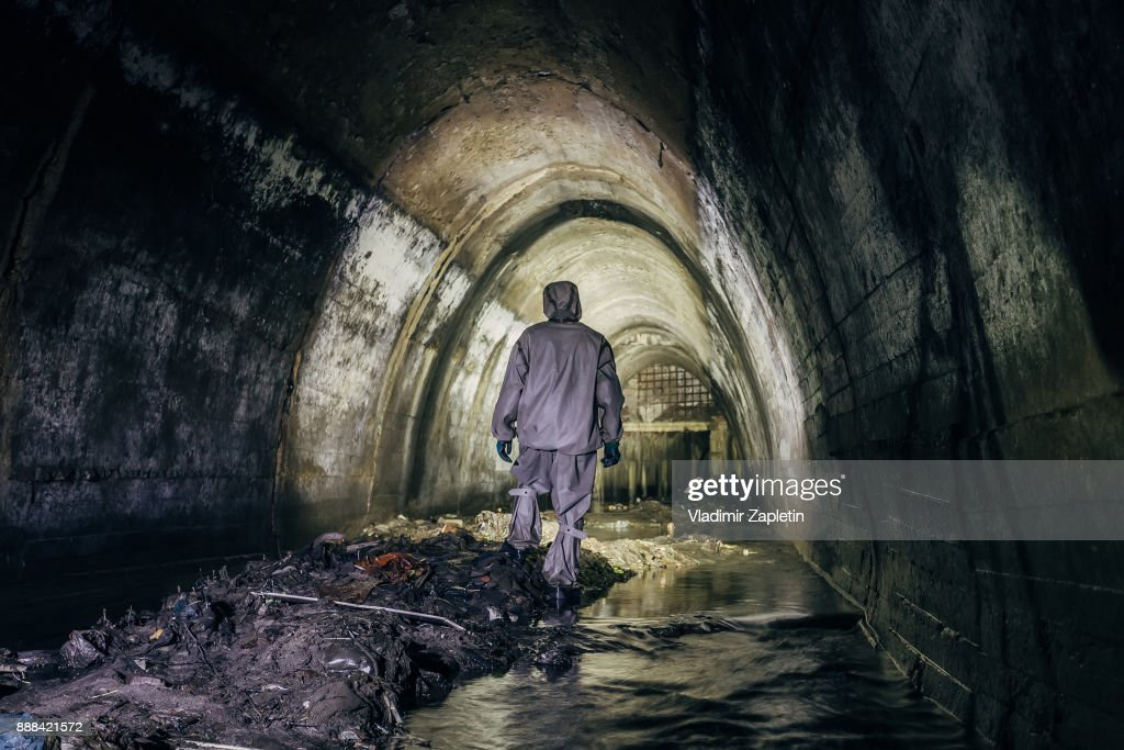Sewer tunnel worker in chemical protective suite in underground gassy sewer tunnel : Stock Photo