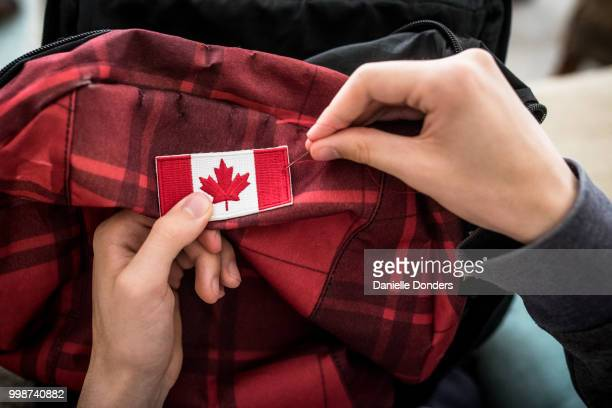 Sewing a Canadian flag onto a backpack for international travel