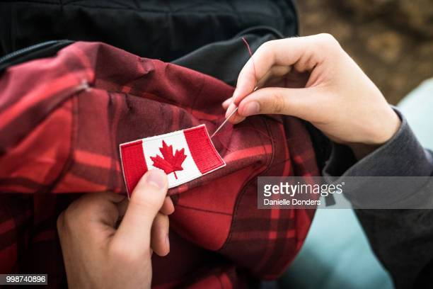 sewing a canadian flag onto a backpack for international travel - canadian culture stock pictures, royalty-free photos & images