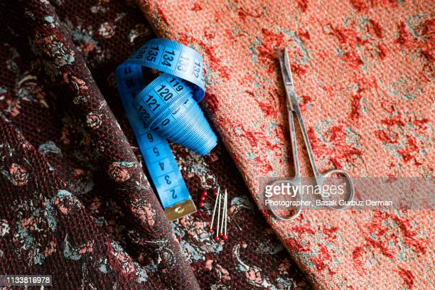 Sewing items; fabric, tape measure, ball head sewing needles, and scissors.