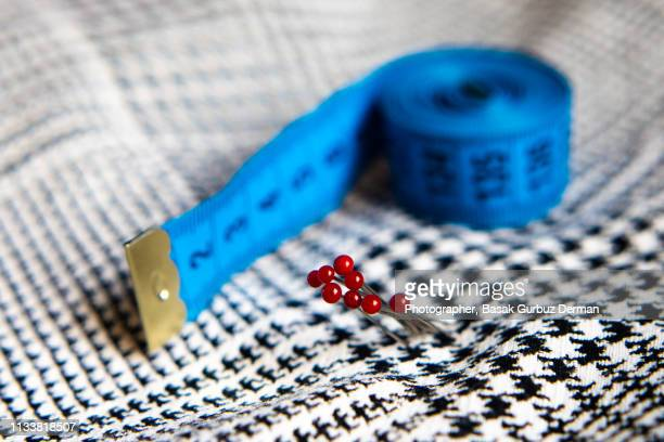 Sewing items; fabric, tape measure, ball head sewing needles.