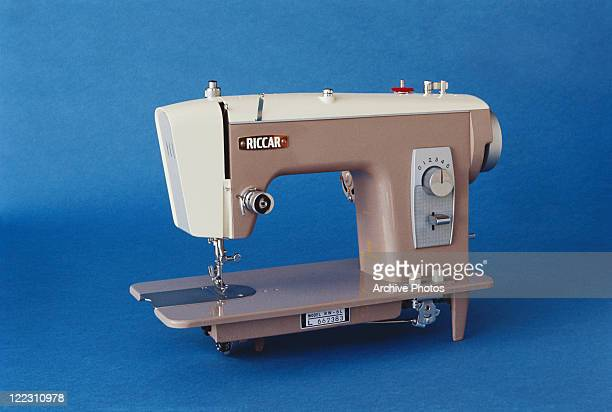 Sewing machine against blue background, close-up