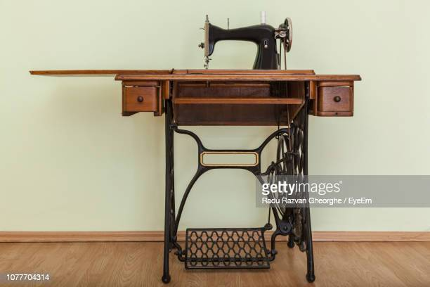 sewing machine on hardwood floor against wall - sewing machine stock pictures, royalty-free photos & images
