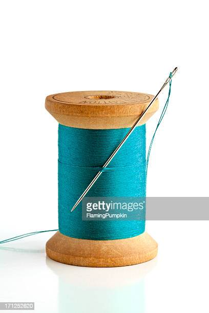 Sewing needle and wood spool of thread. On White.
