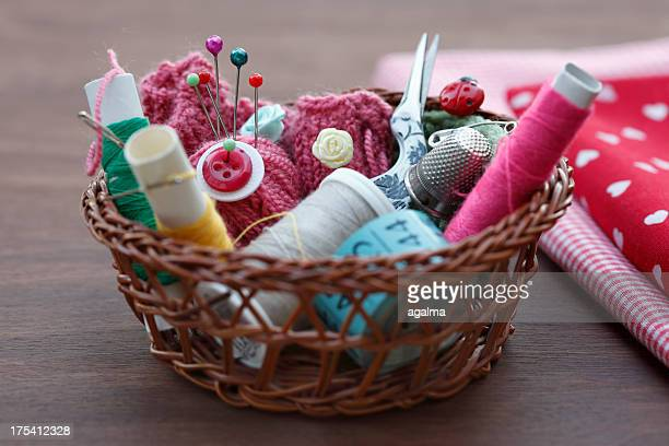 sewing tools in basket with fabric - knoop naaigerei stockfoto's en -beelden