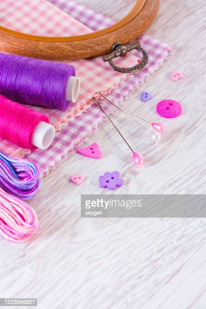 sewing tools: threads, cell fabrics, buttons, ribbon on white wooden table background - ribbon sewing item stock pictures, royalty-free photos & images