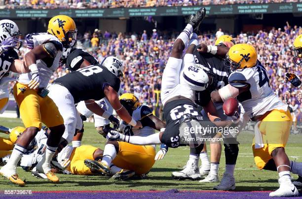 Sewo Olonilua of the TCU Horned Frogs dives into the end zone to score a touchdown against the West Virginia Mountaineers in the first half at Amon G...